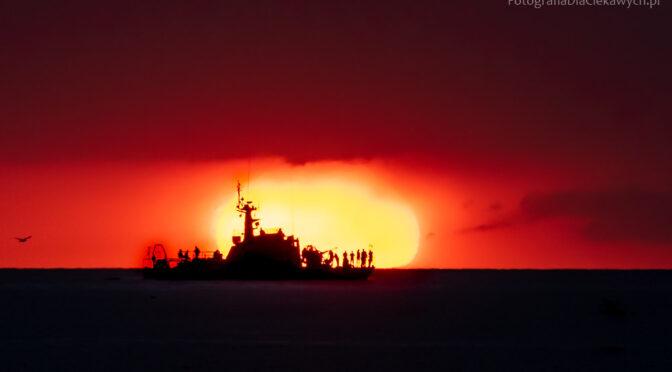 okręt na tle słońca o zachodzie słońca