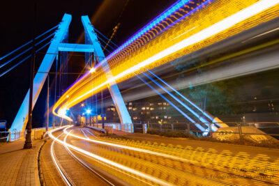 podświetlony most ismugi świateł odtramwaju - zdjecie nocne